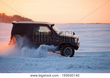 KHABAROVSK RUSSIA - JANUARY 28 2017: Suzuki Jimny moving on ice of a frosn river at sunset