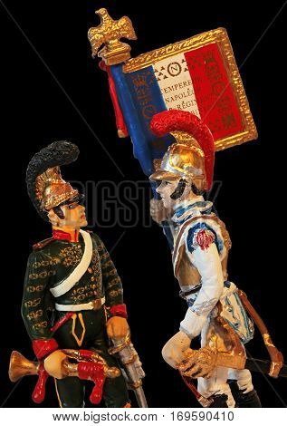 Two old tin toy soldiers from Napoleonic Wars French army. Trumpeter and color guard against black background.