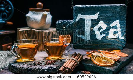 Tea shop with wood hanging sign. Teacups and spices on wood counter