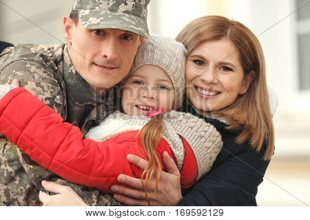 Soldier in camouflage meeting his family outdoors