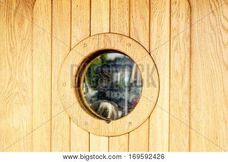 Marine ship window or porthole on wooden wall