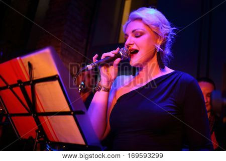 Beautiful woman of band is singing at musical bar, two musicians stand behind she