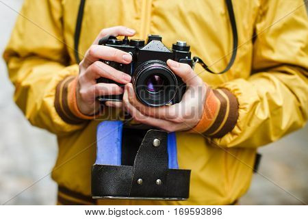 A young guy hipster, holding oldschool film camera, day outdoors, close up, center frame, makes photo