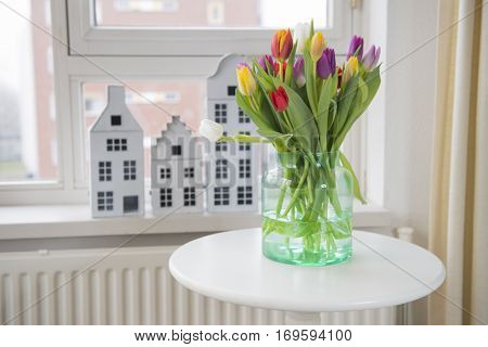 Colorful vase with tulips in interior