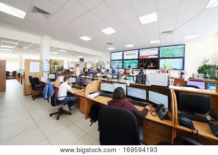 MOSCOW, RUSSIA - APR 25, 2016: Workers are sitting in workplaces with partitions near big screens in Moscow city telephone network