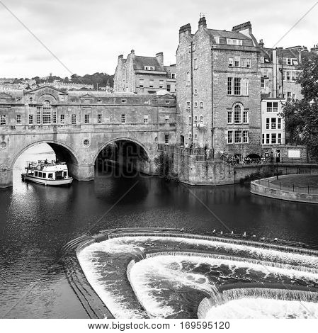 Bath, Somerset, United Kingdom - June 19, 2006: A river cruise tour boat ferries passengers along the River Avon. The Pulteney Bridge (Georgian architecture) over the river Avon with weir in Bath. Black and white.