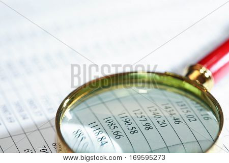Closeup of magnifying glass on paper background with digits