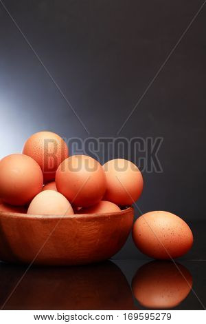 Set of raw brown eggs in wooden bowl against dark background