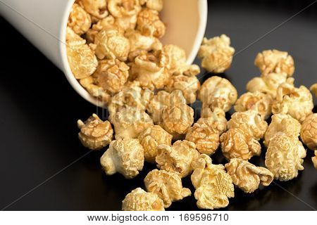 Popcorn on the table. Paper cup with popcorn on black background