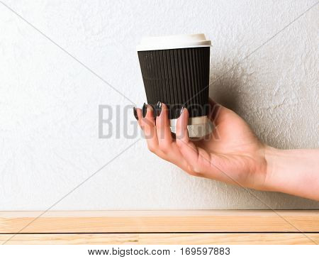 Paper Or Plastic Coffee Cup In Hand On Textured Background