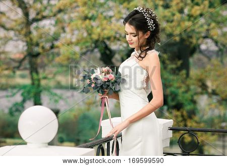 Closeup portrait of young gorgeous bride. Pretty beautiful bride with beautiful bouquet of flowers standing in balcony of amazing mansion on spring tress background. Pretty bride with hairstyle.