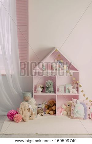 in a pink children's room closet with shelves with different toys