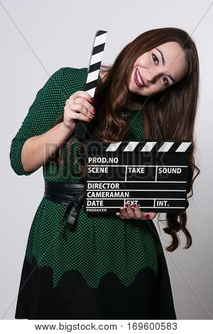 Beautiful Young Girl In Dress Is Holding A Clapperboard