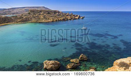 Malta - Snorkeling man and sail boat at Ghajn Tuffieha bay on a hot summer day with beautiful crystal clear sea water