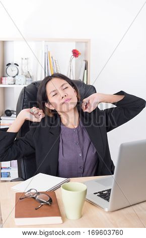 asian businesswoman sitting at the table computer in office with stretching arms.