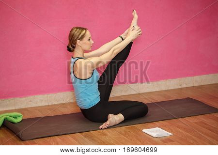 Trainer of fitness or yoga class sport woman doing exercise in gym