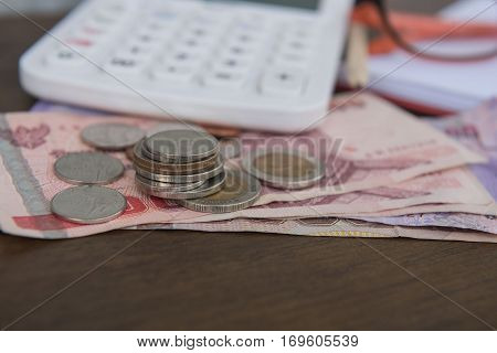 Business on financial report . Closeup coin and banknotes and Calculator , book on wooden background.
