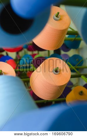 Textile industry - yarn spools on spinning machine in a textile factory. Raw materials for textile industry