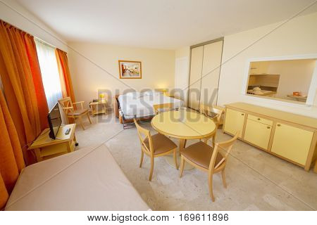 Empty hotel light room with white double bed, tv and dining table