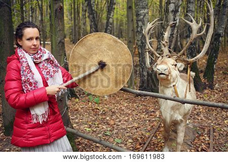 Woman in red with gong and beautiful deer in yellow autumn forest