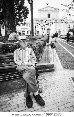popayan, colombia - November, 27th, 2015 - senior man sitting on the bench in white city popayan colombia south america