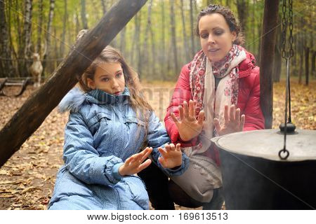 Woman and daughter sit near fire with hanging pot in autumn dry forest