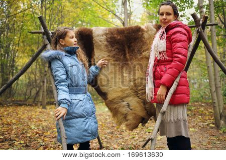 Woman and girl stands near animal skin drying on wooden stakes in autumn forest