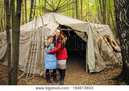Woman and her daughter stand near Chukot yurt with sleds in autumn forest
