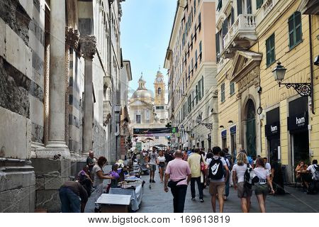 GENOA, ITALY - JUL 21, 2016: People walk down street near Church Chiesa del Gesu, Genoa is sixth largest city in Italy with population of 600 000
