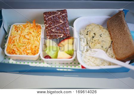 Fresh breakfast in container in airplane - salad, cake, rice, cutlet
