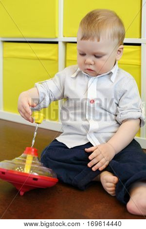 Handsome little barefoot boy sits on floor and plays whirligig in room