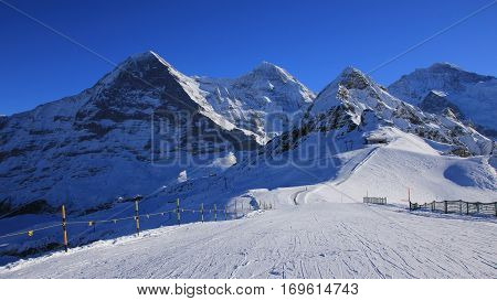 Winter scene in Grindelwald. Ski and snow covered mountaind Eiger Monch Lauberhorn and Jungfrau.