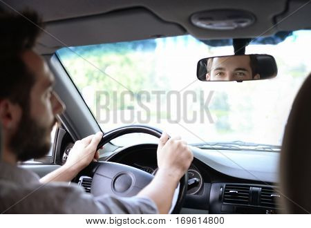Young successful driver looking in rear view mirror