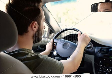 Young successful driver keeping hands on steering wheel