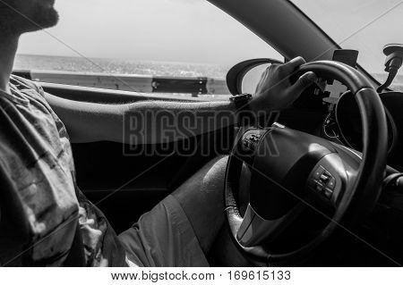 Black and white photo of man driving car
