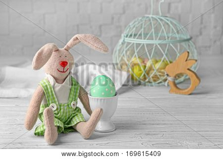 Beautiful bunny and Easter egg on white wooden table