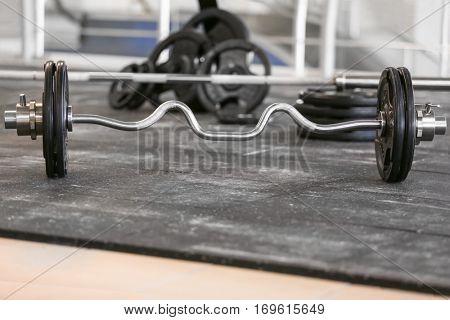 Barbell on dark floor in gym