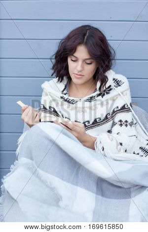 Young beautiful brunette woman wearing nordic style poncho covered in blanket reading a book