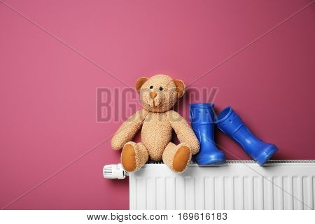 Gumboots and teddy bear on heating radiator on pink background