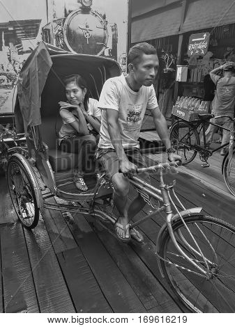 Phra Nakhon Si Ayutthaya Thailand - October 16: Man ride tricycle and woman is passenger in market of Phra Nakhon Si Ayutthaya on October 16 2016