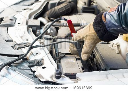 Driver hand wearing warm gloves holding the jump leads next to the flat car battery
