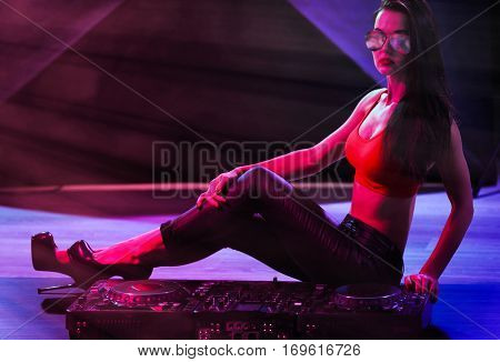 Pretty young woman with DJ console in nightclub