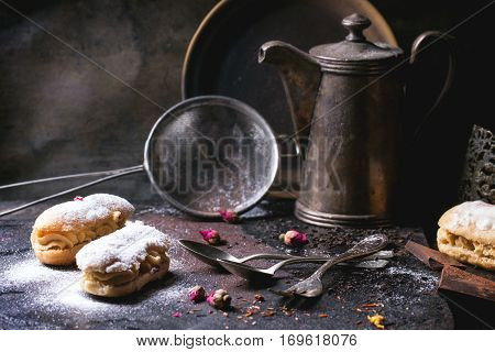 Tea drinking with eclairs and chopped chocolate, served with vintage teapot and cutlery over dark background. See series