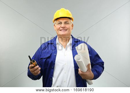 Senior engineer with portable radio transmitter and drawings on light background