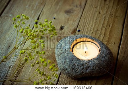 Stone candle holder with tea light on aged wood background, delicate spring yellow flowers, Easter, tranquility concept,meditation