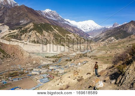 Young woman looking at the beautiful mountain landscape with a Manang village on Annapurna circuit trek in Himalayas, Nepal