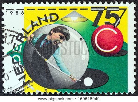 NETHERLANDS - CIRCA 1986: A stamp printed in the Netherlands issued for the 75th Royal Dutch Billiards Association, Checkers Association shows Player in ball preparing to play, circa 1986.