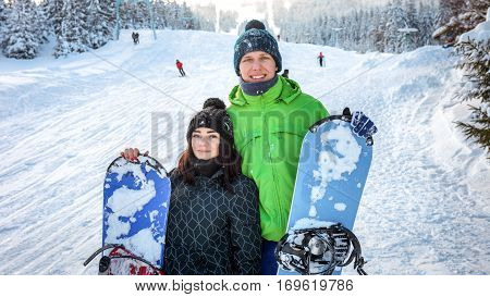 couple snowboarders standing on ski smiling and holding the board on the snow for skiing