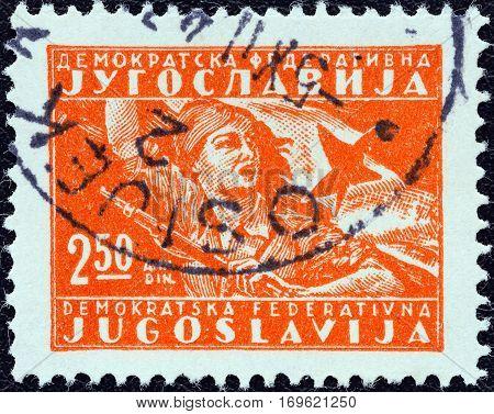 YUGOSLAVIA - CIRCA 1945: A stamp printed in Yugoslavia shows girl with flag, circa 1945.
