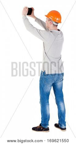 Backview of an engineer in construction helmet stands and enjoys tablet or using a mobile phone. Standing young guy. Rear view  collection.  backside view of person.  Isolated over white background.